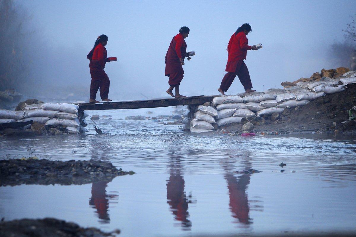Des fidèles traversent la rivière Salinadi pour exécuter des rituels lors du premier jour du Swasthani Brata Katha ( AP Photo / Niranjan Shrestha )