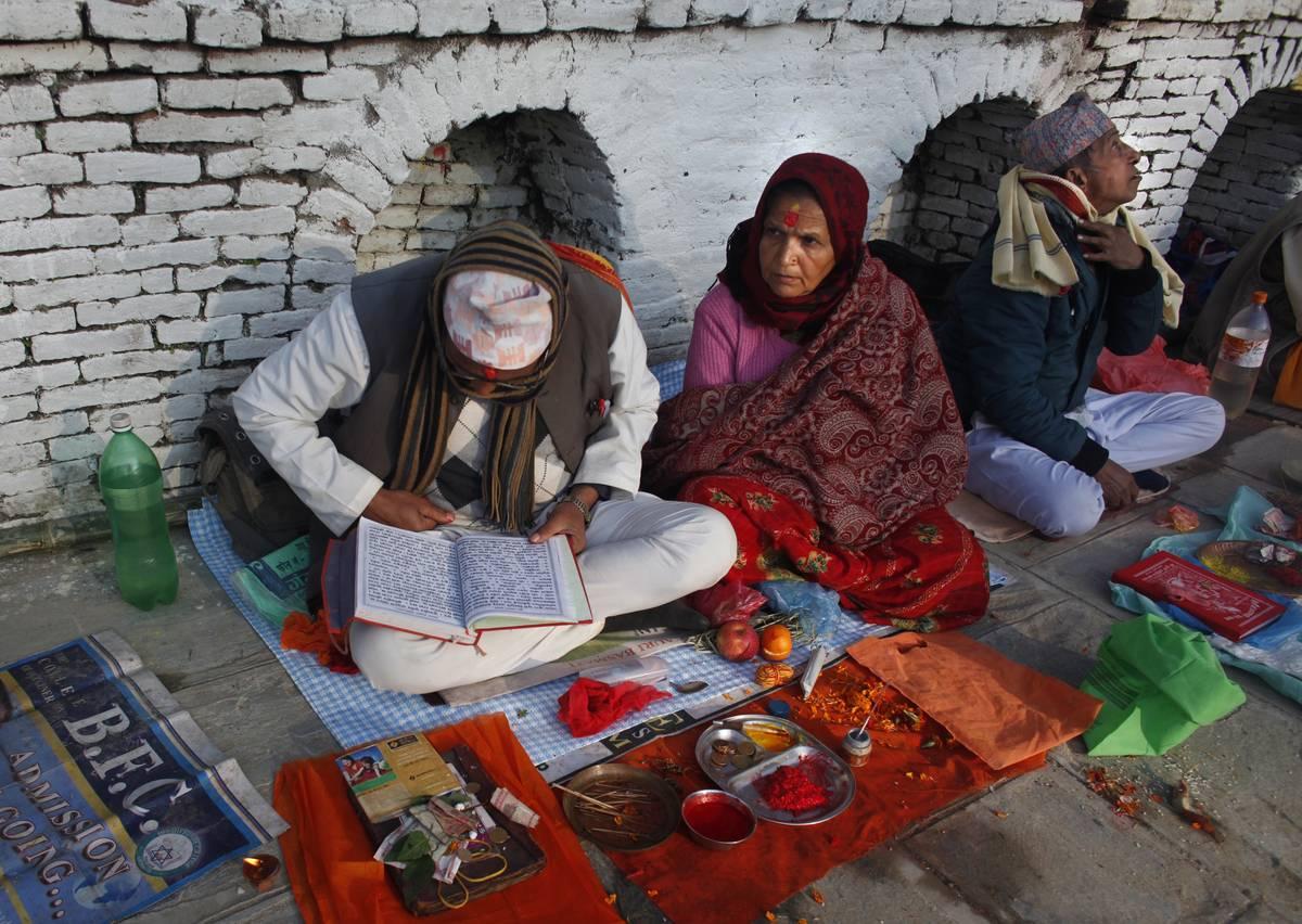 Un prêtre népalais récite un chapitre du livre saint sur la rive de la rivière Salinadi ( AP Photo / Niranjan Shrestha )