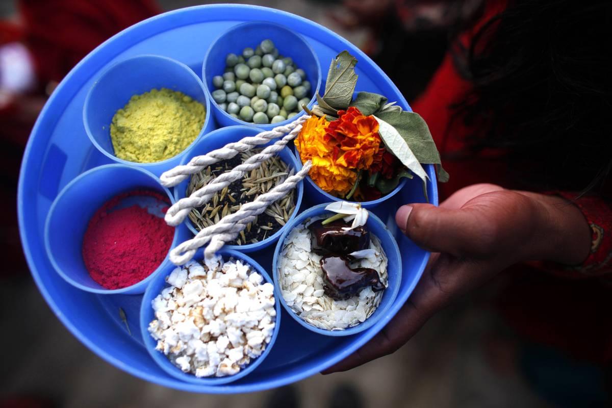 Une femme népalaise tient un récipient contenant différents produits destinés à des rituels (AP Photo / Niranjan Shrestha)