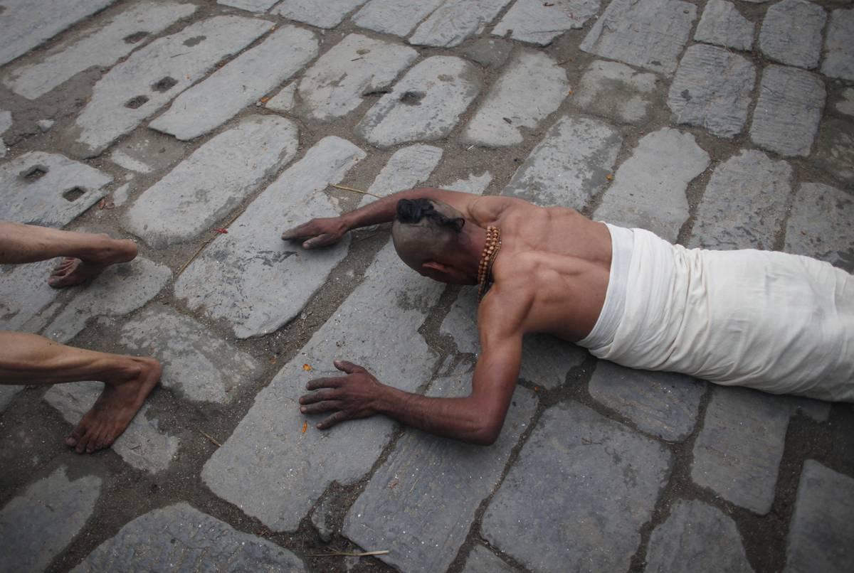 Un fidèle se prosterne afin de pouvoir prier  ( AP Photo / Niranjan Shrestha)