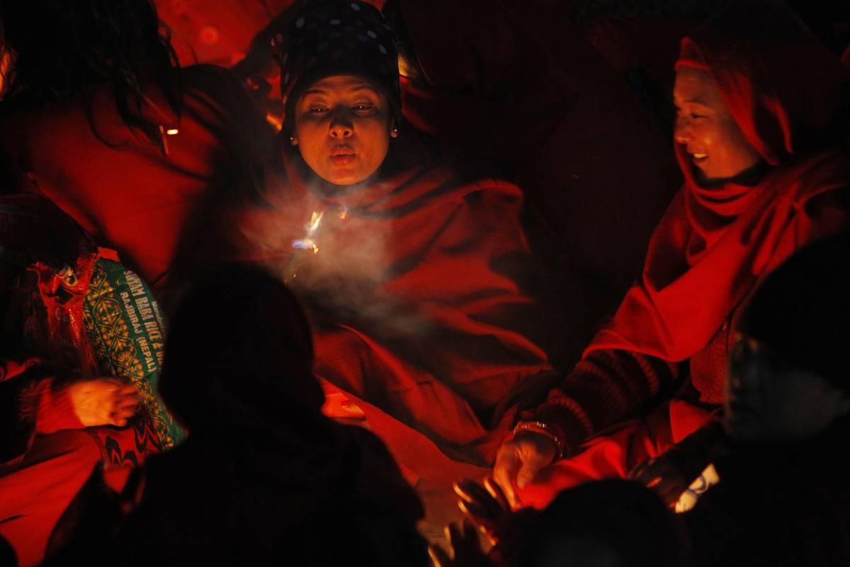 Des népalaises assises autour d'un feu pour se réchauffer avant qu'elles ne prennent leur bains sacré dans la rivière Salinadi (AP Photo / Niranjan Shrestha)