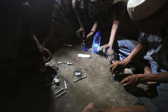 Heroin addicts prepare heroin before using it in Lamu