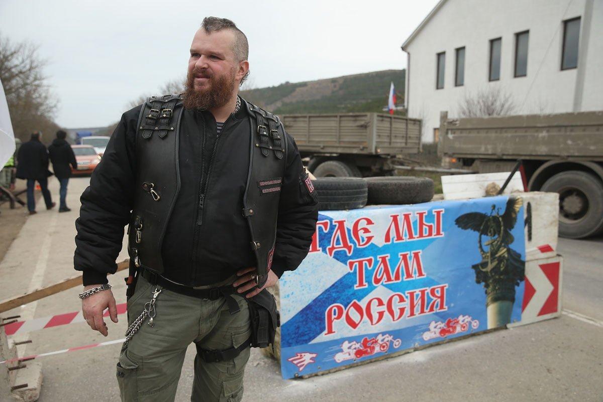 """Un membre des Loups de la Nuit gardant un checkpoint en Crimée, non loin de Sébastopol. Derrière lui, on peut y voir une affiche avec pour inscription : """"Où nous nous trouvons,il y a la Russie"""". Sean Gallup/Getty Images"""